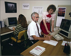 Photo of a man and a woman from the 1990s next to a PC.