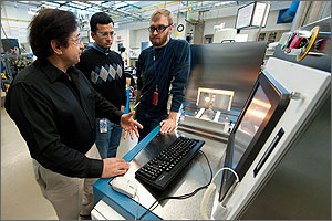 In this photo, three researchers are standing behind the Optical Cavity Furnace, which is a gray-silver box-like structure the size of a small refrigerator