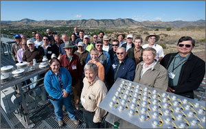 In this photo, about 30 scientists, technicians and engineers have gathered for a group photo, with instruments in the foreground and mountains and blue sky in the background.
