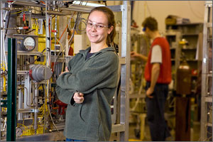 Photo of a woman wearing safety glasses standing in front of machinery in a pilot plant.