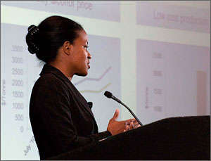 Photo of a woman giving a presentation in front of a screen covered in charts.
