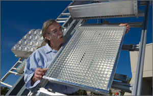In this photo, a scientist in safety glasses examines a rectangular solar module that has the texture and color of silver aluminum foil.