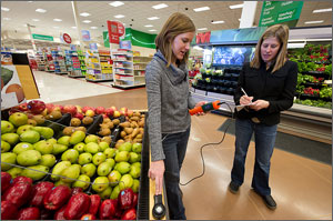 Photo of two women taking light readings in the produce section of a retail store.