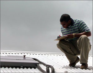 This photo shows a young man on an aluminum rooftop crouching as he looks at a solar collector and writes some data on a clipboard.