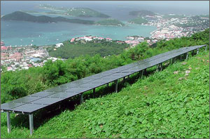 In this photo, a long rectangular chain of solar panels sits in the foreground, surrounded by lush green vegetation. In the background is the Caribbean Sea dotted with large rocks.