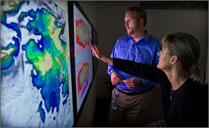 In this photo, a man and a woman are looking at a huge colorful wall map that shows sun resources in yellows and oranges, wind resources in blues.