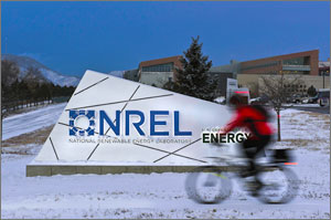 Photo of a bike rider moving in front of an NREL sign.