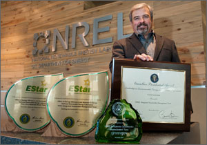 Photo of a man standing near four award plaques.