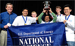 Photo of five young men and their coach standing behind of a banner that says 'U.S. Department of Energy – National Science Bowl.'  They are holding the trophy for winning the competition above their heads.