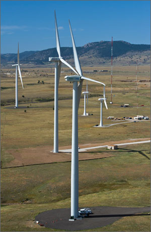 An aerial photograph of the National Wind Technology Center site shows three large wind turbines with other smaller wind turbines in the background. Mountains are in the background of the photo behind the site.