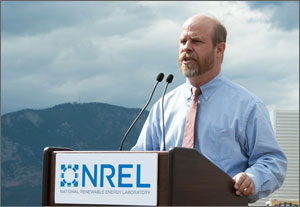 The director of the National Wind Technology Center speaks at a podium during a ceremony at the center for the new dynamometer facility. The podium displays the NREL logo. Mountains are in the background.