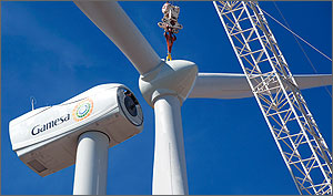 A crane lifts the blades of a wind turbine under construction so that it can be attached to the rest of the turbine