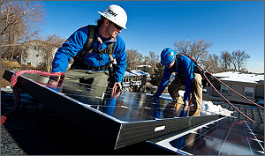 In this photo, men in hard hats, tethered with ropes, carefully maneuver a solar panel next to one that has already been installed on a gently sloping roof.