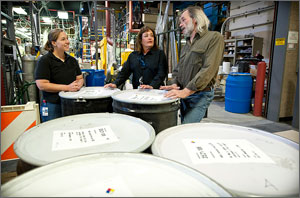 Photo of three people standing near a fuels processing area near sealed barrels.
