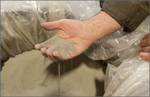 Photo of a man holding grains of sand-looking catalyst.