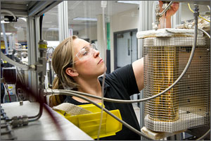 Photo of a woman in a lab with a small reactor.