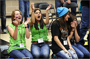 In  this photo, the two girls on the left are on their knees, in green T-shirts,  raising their hands in celebration. The two girls on the right, in black  T-shirts, have different reactions, one a look of resignation, one with her  face buried in her hands.