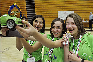 In this  photo, three eighth-grade girls in green T-shirts beam as they hold up a green  car that is about eight inches long.