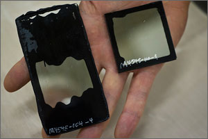 This is a close-up of a square and a rectangular sample held in a hand. The rectangular sample shows failure in the form of black globs invading the transparent center.
