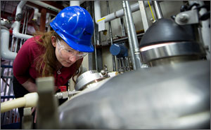 Photo of a woman in a hard hat looking into a fermenter.