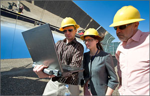 This photo shows three people in yellow hard hats looking at a laptop computer screen, with parabolic mirrors in the background.
