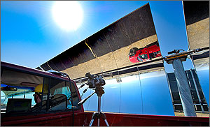 In this photo, a red pickup rumbles alongside a row of parabolic-shaped mirrors while the upside-down reflection of the truck is visible along the upper sections of the mirror.