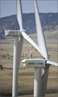 Photo of a giant wind turbine, with a man standing on the turbine's nacelle.