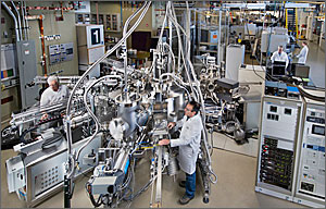 This photo shows two men in white lab coats amid gleaming silver machinery with hoses heading to an unseen ceiling.