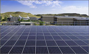 Photo of solar panels in the foreground with the NREL campus in the background, along with the grassy mesas beyond.