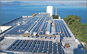 This photo shows several rows of tilted solar panels in the foreground, with the blue waters of the San Francisco Bay and the leafy forest of the California mainland in the background.