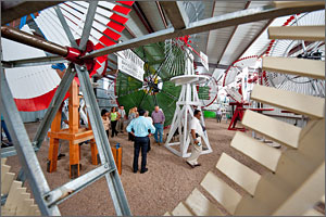 This photo shows several people assembled in a barn with the brightly colored blades of vintage windmills surrounding them.