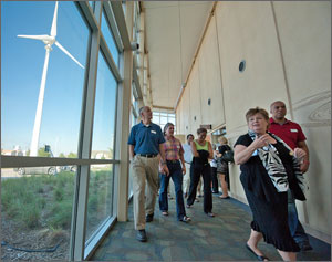 In this photo, a woman leads a half dozen others down a corridor lined with glass windows. Through the windows, a large, white wind turbine can be seen.