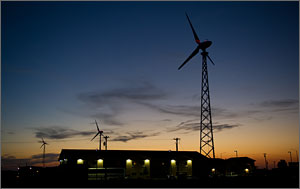 This photo is in twilight, with the setting sun contrasting with the dark clouds. In the foreground is a low-rise hotel, with wind turbines behind.