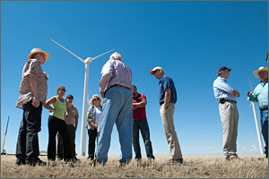 In this photo, seven people listen to a man with his back to the camera. In the background are a wind turbine and a brilliant blue sky.