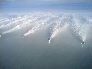 In this photograph of an offshore wind farm, wake turbulence behind wind turbines is visible because of fog in the air.