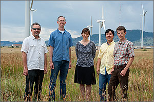 Five people (the members of the team doing wind plant aerodynamics modeling and simulation work) stand in a field with four large wind turbines behind them.