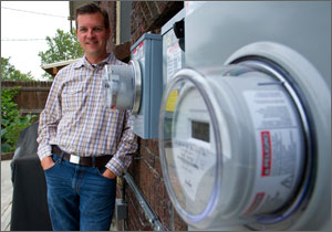 In this photo, a man in a checked shirt leans against the side of his house, while, in the foreground are two cylinder-shaped utility meters.