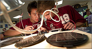 In this photo, a beige wire in the foreground bisects two high school students dressed in their red school colors. Below the wire are solar arrays that the students are testing with wire probes and artificial light.