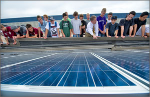 Photo of 18 students leaning over a ledge looking at solar panels while their teacher, in a white shirt and tie, points to a panel.
