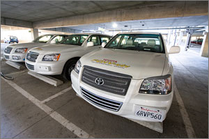 This photo shows three white Toyota SUVs lined up in parking places in NREL's parking garage. The vehicle in the forefront is an advanced fuel cell hybrid vehicle that can operate using hydrogen.