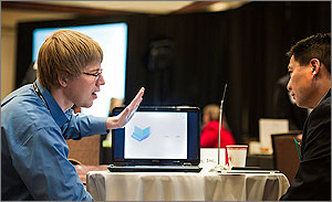 In this photo, a man in a blue shirt and glasses uses his left hand to make a point to a man across the table, who is wearing a suit. Between them is the bright glow of a laptop computer.