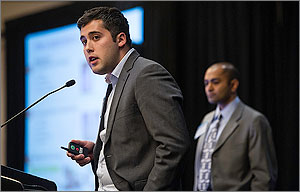 In this photo, a man in a suit stands at a podium, holding a device that changes the images on a screen in the background. Also in the background is another man.
