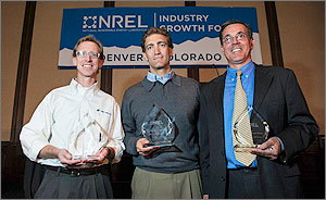 In this photo, three men stand in front of the NREL Industry Growth Forum banner holding trophies