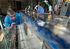 In this photo, a scientist in a blue shirt peruses a row of hundreds of membranes arranged like file folders in a prototype of the DEVAP cooling unit.
