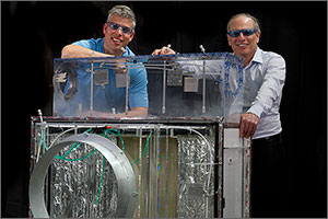 In this photo, two men stand behind a jukebox-sized prototype of an air conditioner made of glass and gray metal.