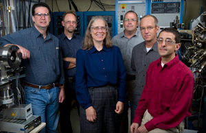 In this photo, five men and one woman stand among several large pieces of laboratory equipment.