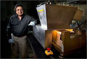 Photo of a scientist standing with his left arm leaning against a silver-metallic instrument; the top half of the instrument is in the shape of a trapezoidal prism.