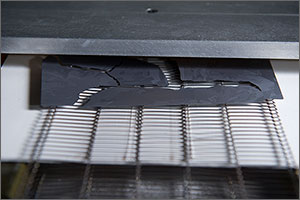 Close-up photo of a gray silicon wafer broken into several pieces of varying size as they emerge from a grid-wired conveyer.
