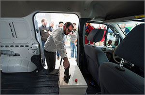 An engineer connects a battery in a research vehicle to a charging station. Behind him, several observers watch.