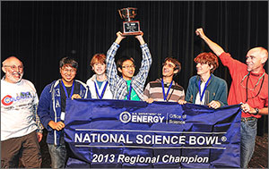 "Two men and five teenage boys stand behind a banner that reads ""U.S. Department of Energy Office of Science National Science Bowl 2013 Regional Champion."" The boy in the center holds a medal over his head."